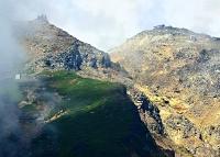 雲間に姿を現した御嶽山の山頂剣ケ峰(右)と王滝頂上(左)。遺族らは二つの頂を結ぶ八丁ダルミを目指す=25日午前10時42分、王滝村