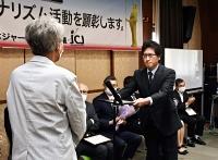 JCJ大賞の賞状を受け取る牛山健一報道部デスク(右)=25日、東京・水道橋