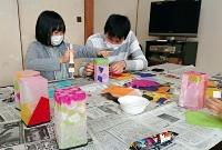 27日の慰霊式で使う灯籠を作る親子=26日午前11時56分、木曽町三岳