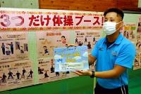 「3つだけ体操」を紹介する冊子を手にする荻野さん