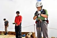 山頂剣ケ峰で噴火時間に合わせて手を合わせる水野さん(右)=27日午前11時52分