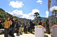 噴火災害の犠牲者を悼み、御嶽山に向かってシャボン玉を飛ばす山びこの会の会員たち=27日午後0時33分、王滝村の松原スポーツ公園