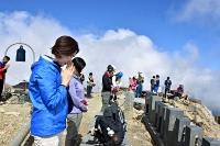噴火した時間に合わせて山頂剣ケ峰で黙とうする人たち=27日午前11時52分