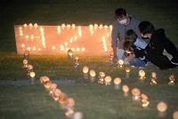 竹灯籠の明かりで犠牲者を悼んだ噴火慰霊式=27日午後6時34分、木曽町三岳の太陽の丘公園
