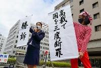 東京電力福島第1原発事故を巡る避難者訴訟の控訴審判決を受け、「勝訴」などと書かれた紙を掲げる原告側の支援者ら=29日午後、高松高裁前