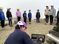 山頂剣ケ峰でタブレット(手前)を通じて所さんに歌声を披露する子どもたち=29日午後1時13分(三岳小学校提供)