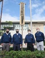 福岡国際センターに設置された、大相撲九州場所を知らせる「御免札」。左端は三保ケ関親方=1日、福岡市