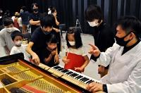 小池さん(右)にピアノの構造を教わる参加者