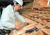 杉板を1枚1枚打ち付けていくこけら葺きの作業