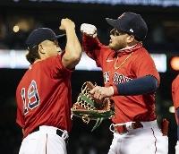 4月、好返球で一走を刺した左翼手のバードゥーゴ(右)と迎えるレッドソックス・沢村=ボストン(ゲッティ=共同)