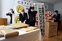 タイムカプセルの木箱(右)から取り出される手紙の入った封筒や垂れ幕など=9日、茅野市