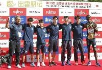 初出場優勝を果たし、記念写真に納まる東京国際大の選手らと大志田監督(左端)=出雲ドーム