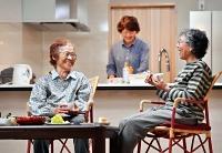 真新しい自宅で小川さん(右)とお茶を飲みながら笑顔で話す渡辺さん(左)。奥は美佐さん=12日午後4時44分、長野市津野