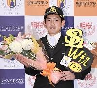 ソフトバンクから1位指名を受け、花束を手に笑顔を見せるノースアジア大明桜高の風間球打投手=10月11日、秋田市