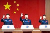 記者会見で手を振る宇宙飛行士の王亜平さん(右)ら=14日、中国・酒泉衛星発射センター(共同)