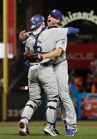 ジャイアンツを破りリーグ優勝決定シリーズへの進出を決め、捕手スミスと抱き合うドジャースのシャーザー=サンフランシスコ(共同)