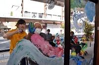 絵の具でガラスに手形を付ける利用者(中央)とサリーさん(左)