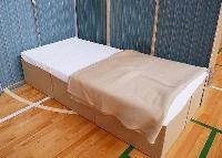 燃えにくい素材のシーツと毛布を掛けた段ボールベッド=7月、北海道北見市(避難所・避難生活学会提供)