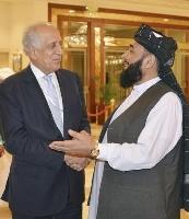 2019年7月、アフガニスタン和平を巡る協議の会場で、言葉を交わす米国のハリルザド・アフガン和平担当特別代表(左)とタリバンのメンバー=カタール・ドーハ(共同)