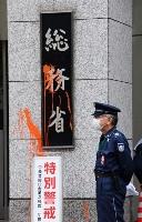 オレンジ色の塗料がかけられた総務省の看板=19日午前、東京・霞が関