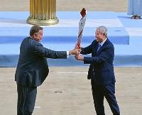 アテネのパナシナイコ競技場で北京冬季五輪の聖火をギリシャ・オリンピック委員会のカプラロス会長(左)から受け取る大会組織委員会の于再清副会長=19日(共同)