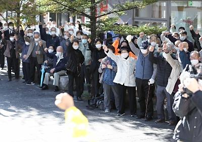 県内小選挙区立候補者の出陣式で、拳を握って気勢を上げる有権者=19日午前9時13分