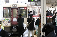 記念ヘッドマークを取り付けた観光列車「おいこっと」。ホームで鉄道ファンが撮影をしていた=23日午前10時、飯山駅
